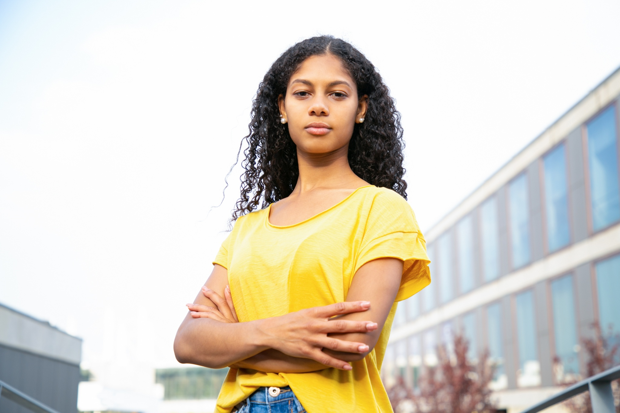Serious confident student girl standing for camera with folded arms. Young Latin woman in bright casual shirt posing in urban settings. Confident woman portrait concept