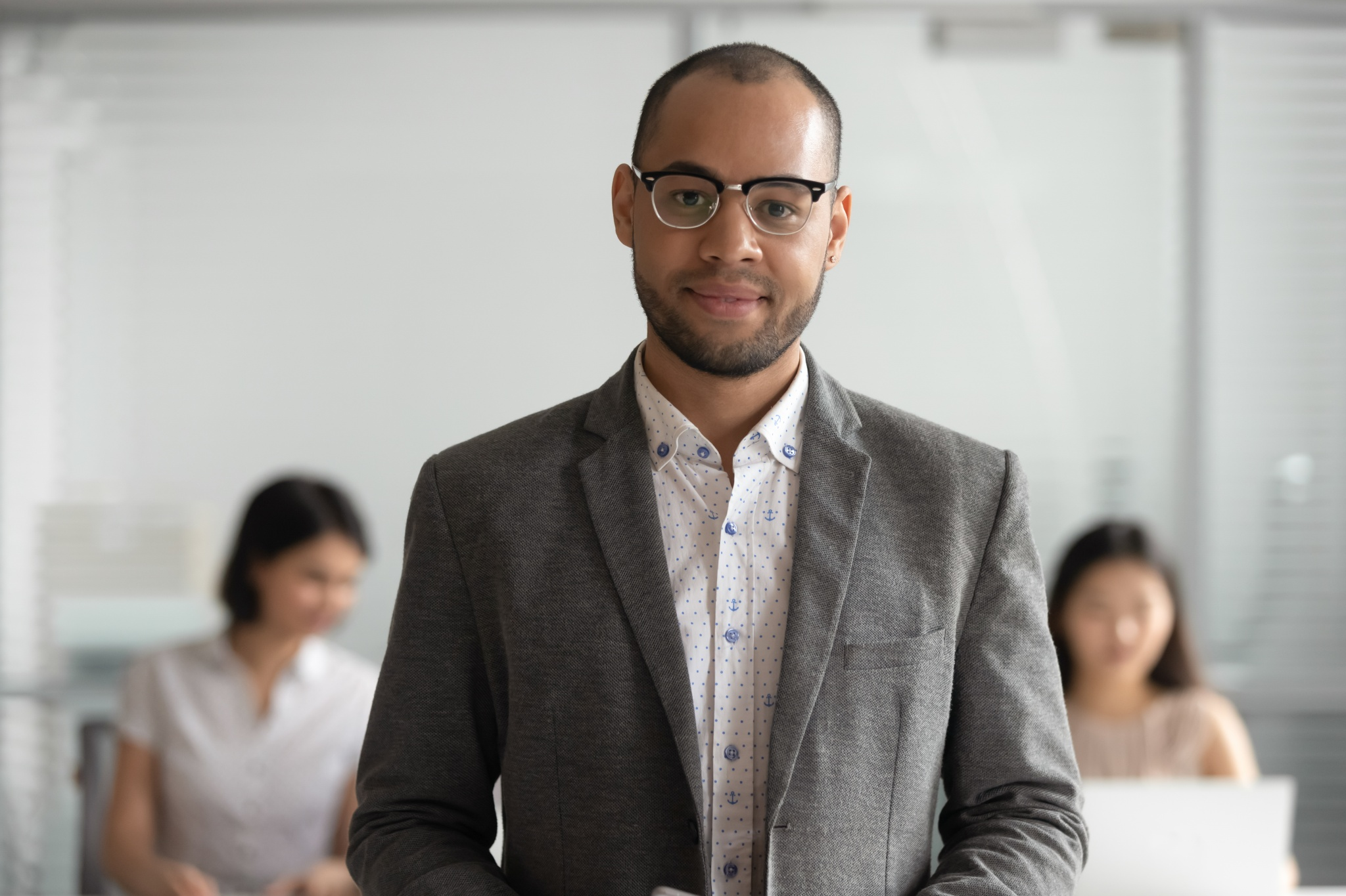 Headshot portrait of smiling biracial male employee in glasses stand forefront look at camera, happy confident businessman in spectacles and suit posing at workplace. Leadership concept