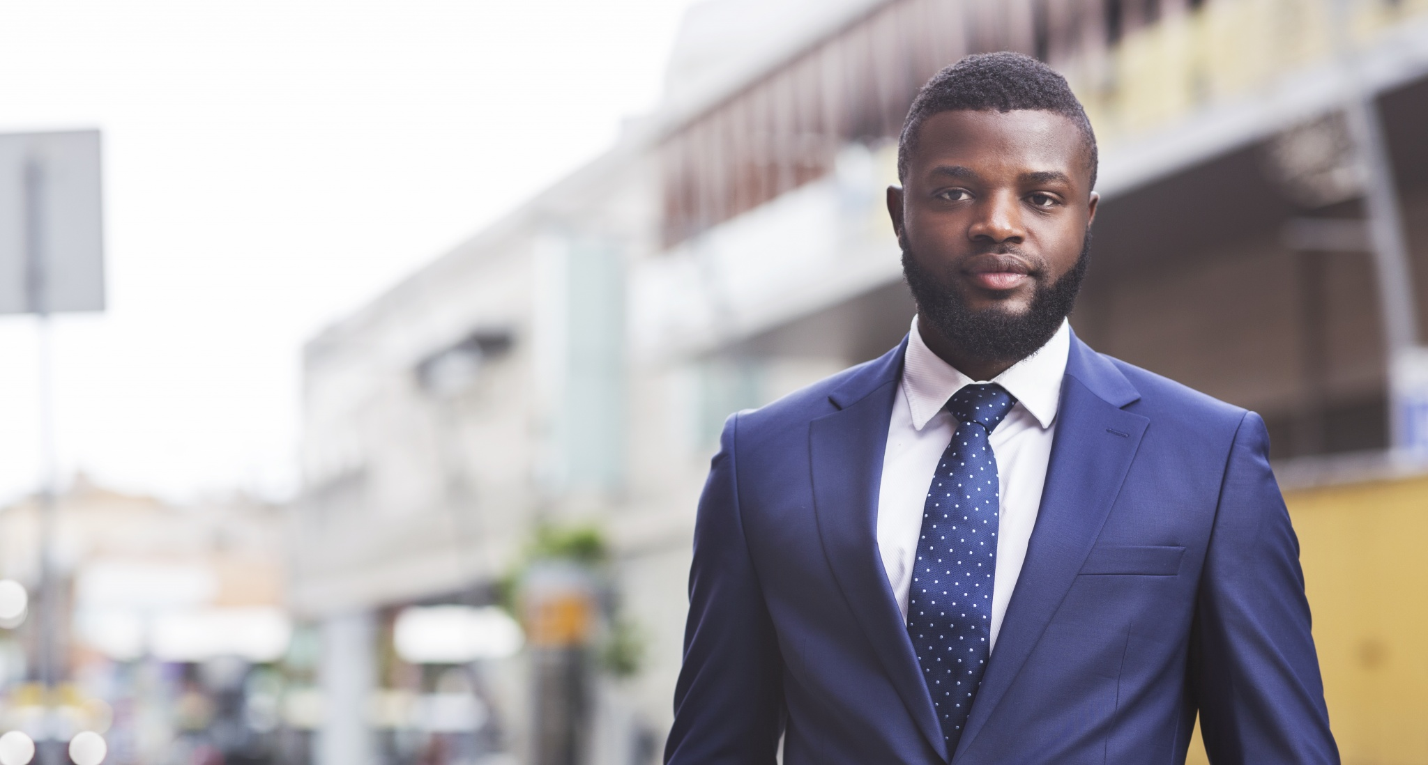 Serious millennial african american employee posing to camera against cityscape, panorama with copy space
