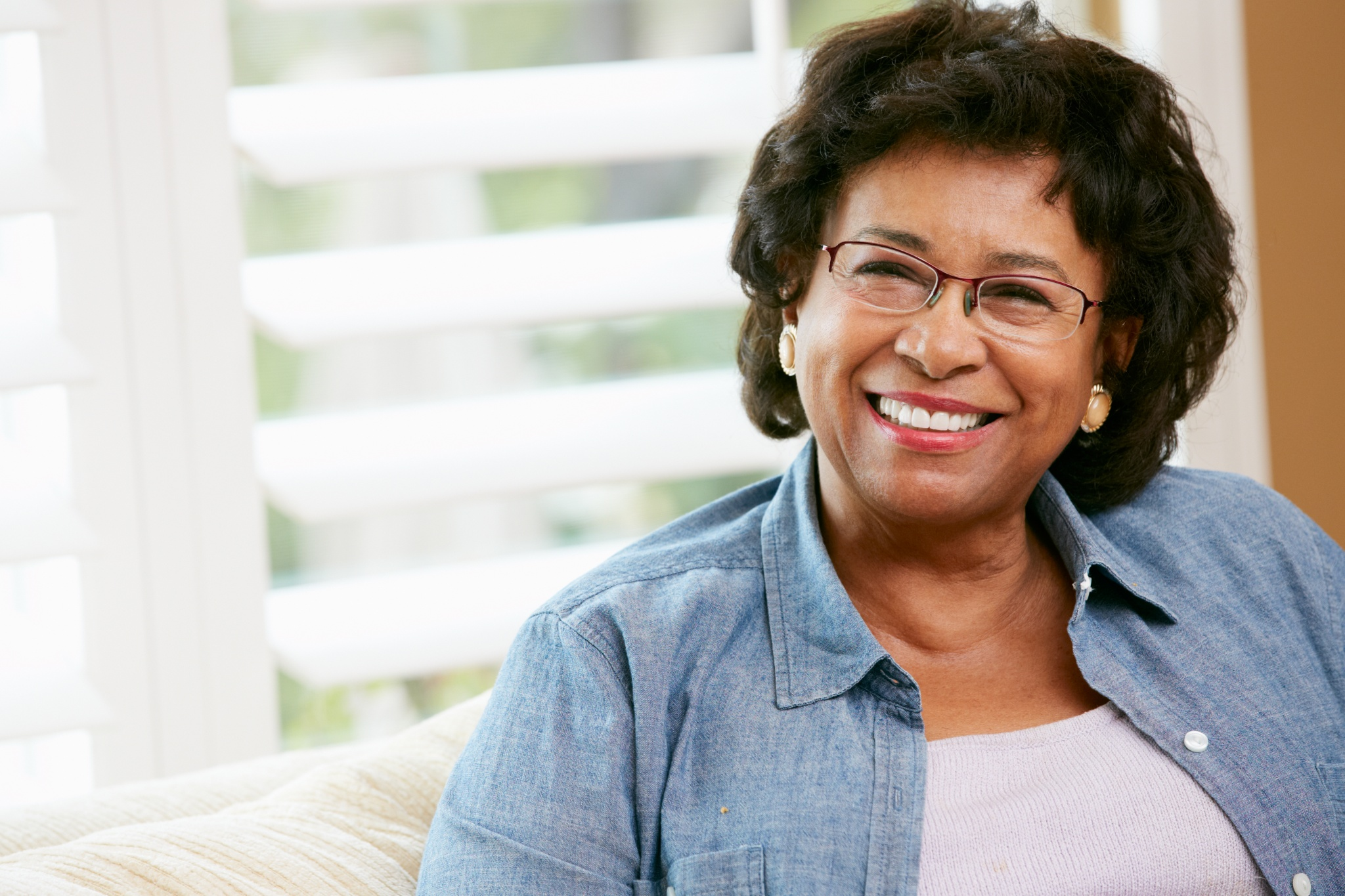 Portrait Of Happy Senior Woman At Home Looking At Camera Smiling