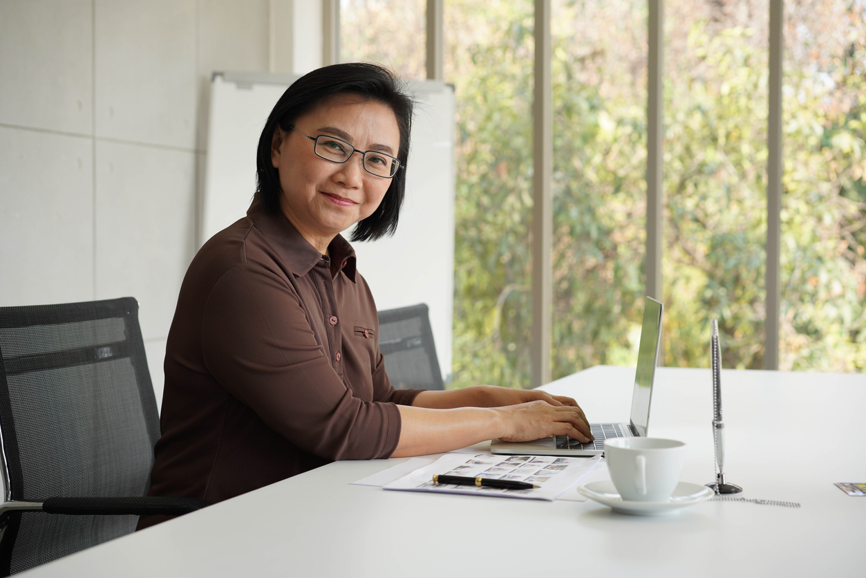 Elderly business asia woman confident with success in front of  laptop in nice office green