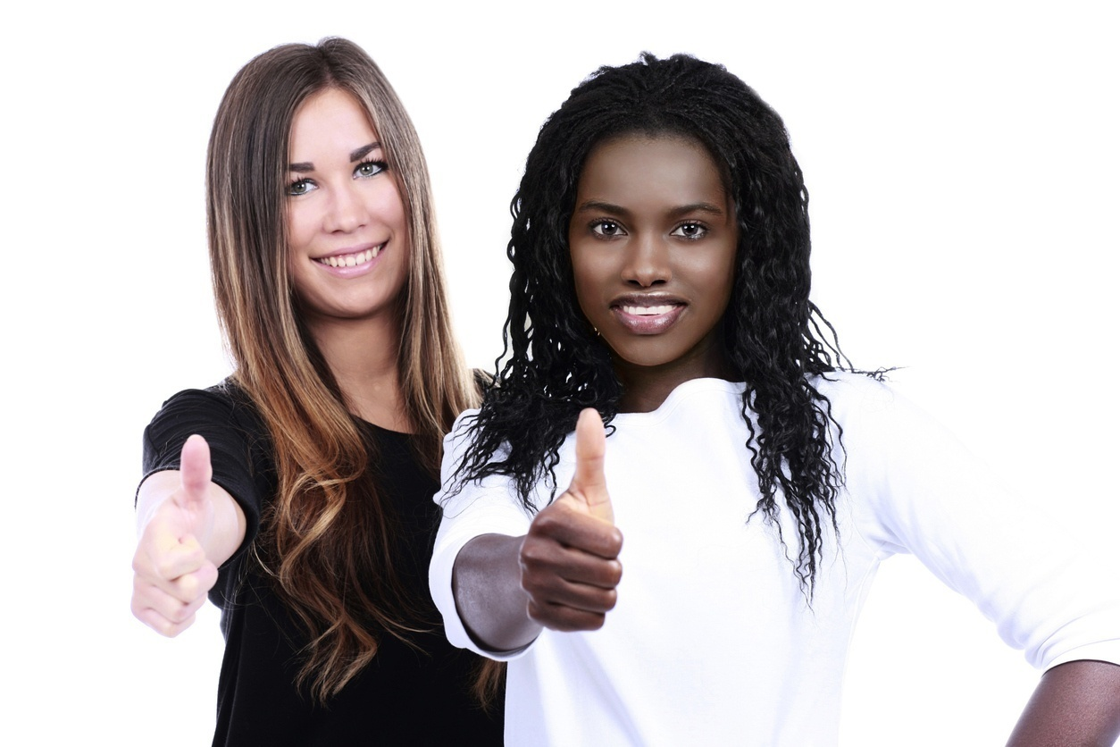 African woman and european woman together with thumbs up