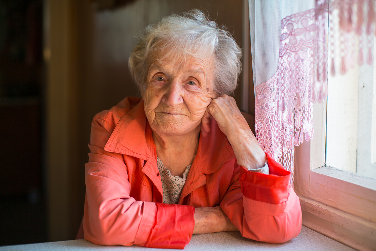 Elderly woman in red jacket sitting at the table in the house.