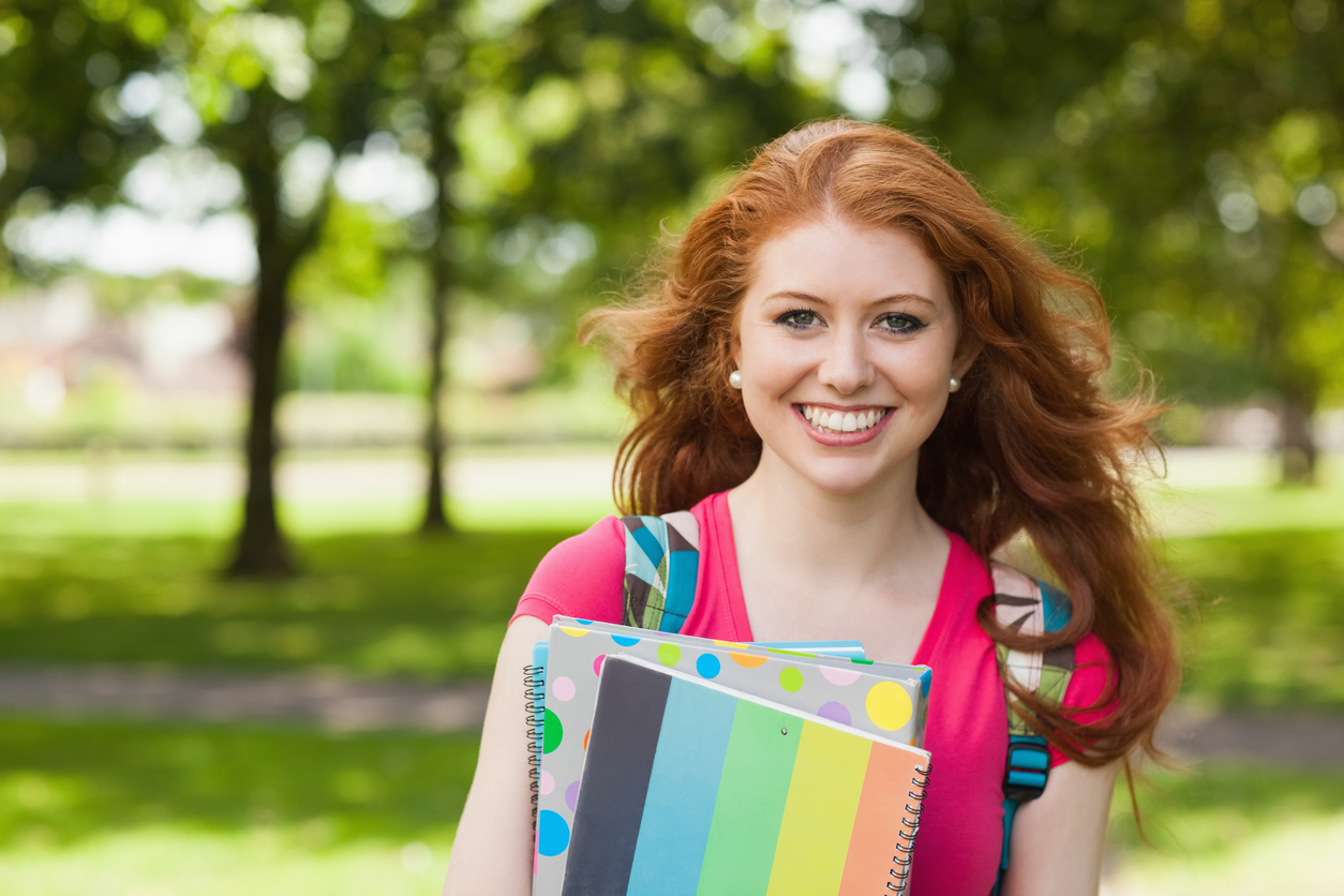 Gorgeous smiling student holding notebooks on campus at college